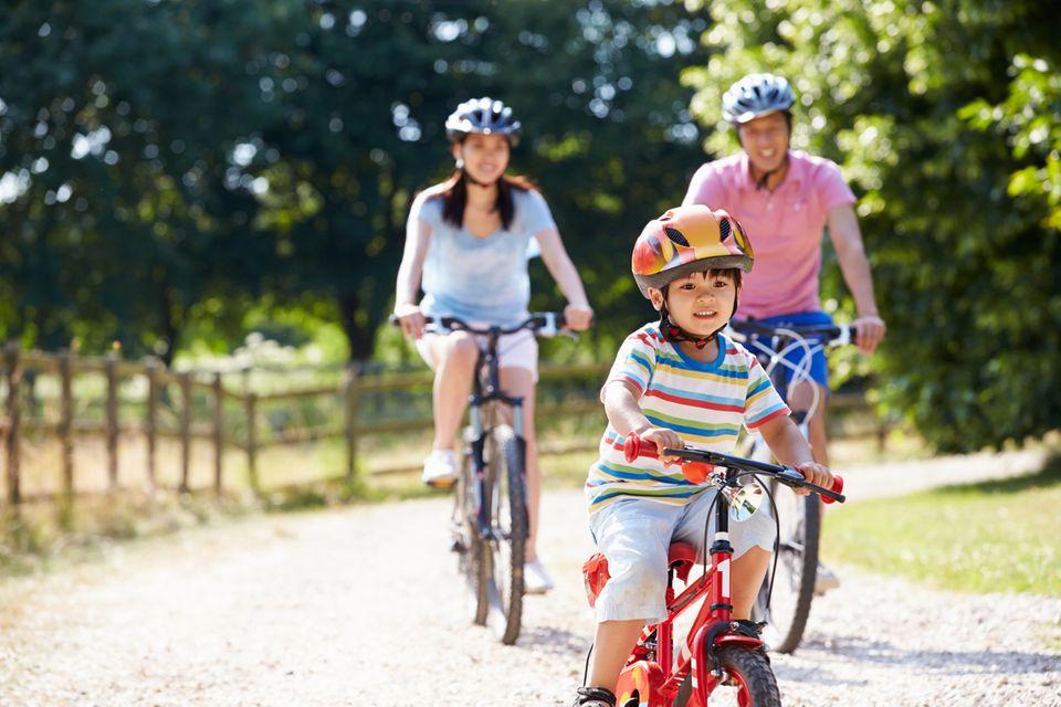 Kleine asiatische Familie fährt Fahrrad