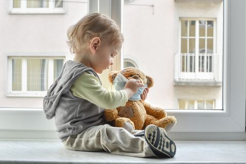 Kind spielt mit Teddy und Maske