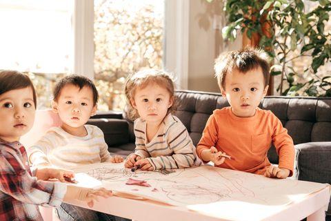 Vier Kleinkinder malen zusammen an einem Tisch