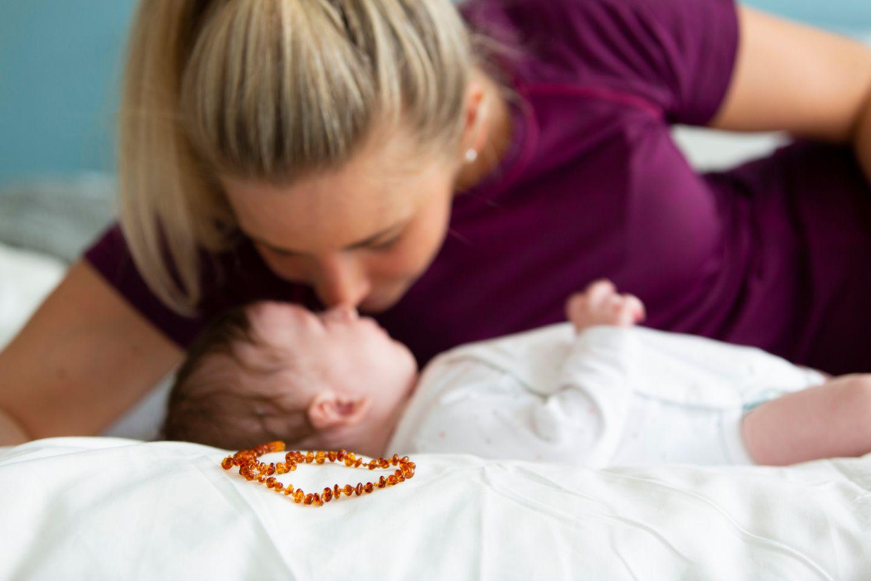 Mutter kuschelt mit Baby und eine Bernsteinkette liegt im Vordergrund