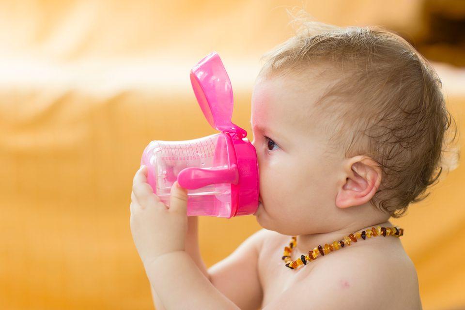Baby mit Bernsteinkette um den Hals trinkt aus einer Trinkflasche