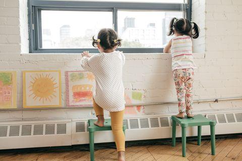 Kleine Mädchen stehen in der Kita am Fenster und gucken raus.