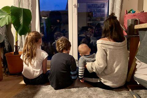 Eine Mutter sitzt mit ihren drei Kindern in Corona-Quaratäne vor dem Fenster