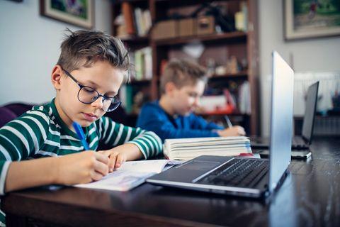 Zwei Jungen lernen im Fernunterricht mit Laptop und anderen Materialien