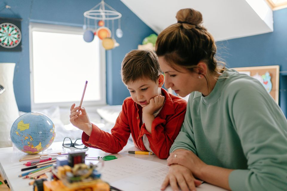 Eine Junge und seine Mama versuchen sein Lernmaterial zuhause durchzuarbeiten