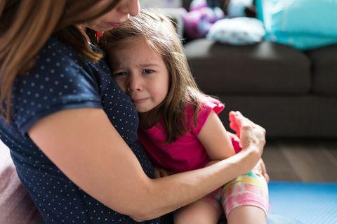 Weinendes Mädchen sitzt auf dem Schoß einer liebevollen Frau
