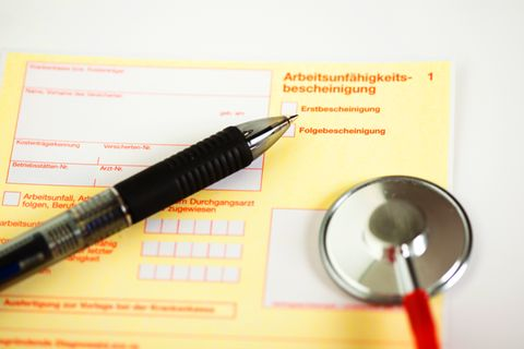 Arbeitsunfähigkeitsbescheinigung mit Kugelschreiber und Stethoskop