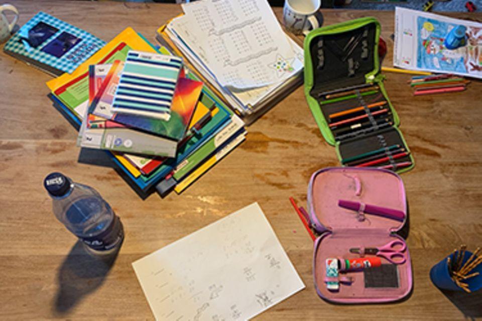 Der Esstisch im Homeschooling ist voller Schulmaterialien