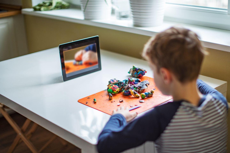 Junge macht ein Knetprojekt vor dem Tablet