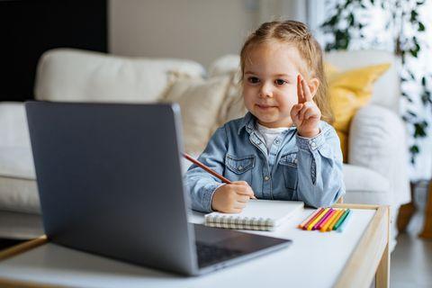 Kleines Mädchen übt vorm Laptop Beudeutungen von Gebärden und malt diese