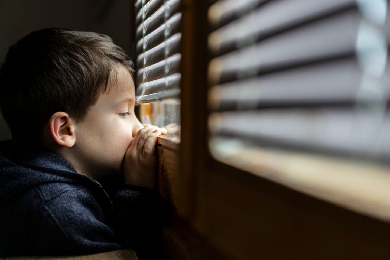 Kleiner Junge schaut sehnsüchtig aus dem Fenster