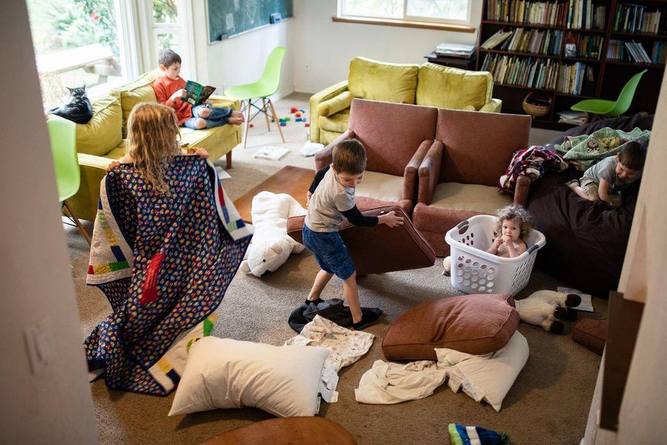 Kinder einer großen Familie nehmen im Lockdown das Wohnzimmer auseinander
