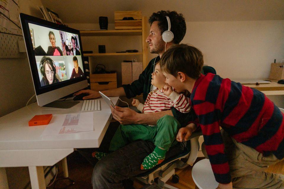 Ein Vater befindet sich in einer Videokonferenz, seine beiden Kinder schauen zu