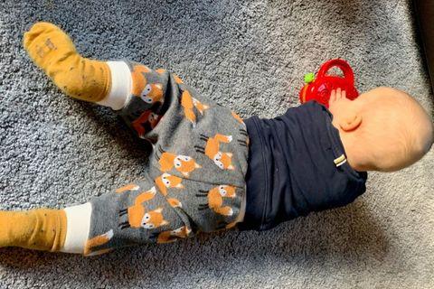 Baby liegt auf dem Teppich