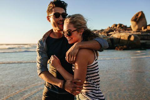 Junges verliebtes Paar geht im Sommer am Strand spazieren