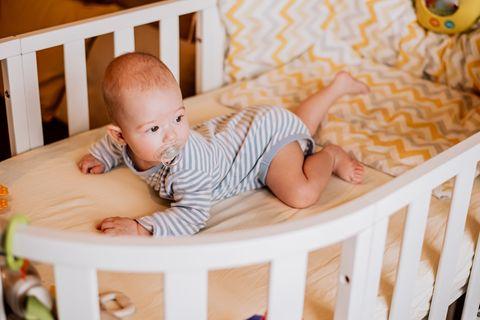 Baby liegt auf dem Bauch in der Babykrippe