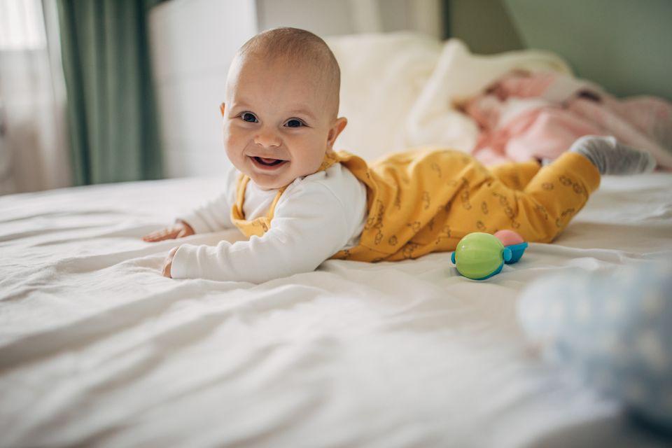 Baby liegt auf dem Bauch und lacht