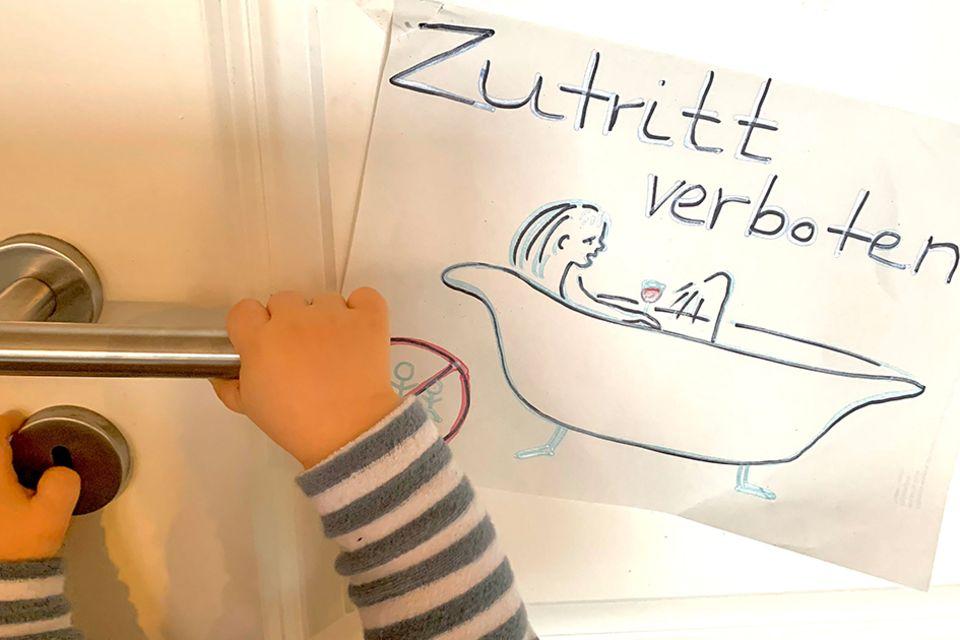 """Schild am Badezimmer: """"Zutritt verboten"""", darauf eine Zeichnung der badenden Mutter. Baby drückt die Türklinke runter."""