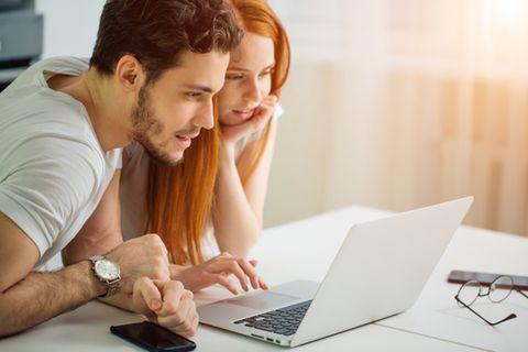 Ein Paar informiert sich am Laptop über den Kinderbonus