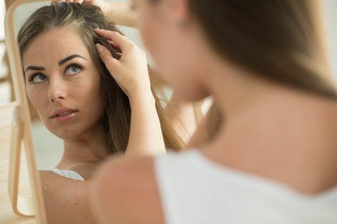 Eine Schwangere schaut sich ihren Haarausfall im Spiegel an