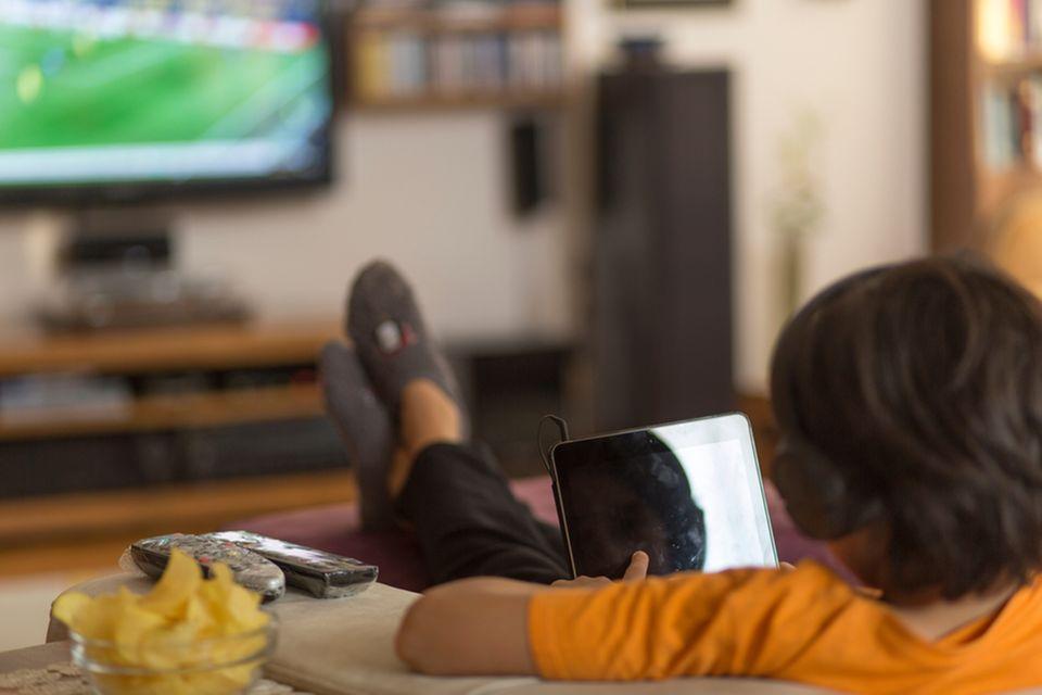 Junge sitzt vor dem Fernseher und isst Chips.