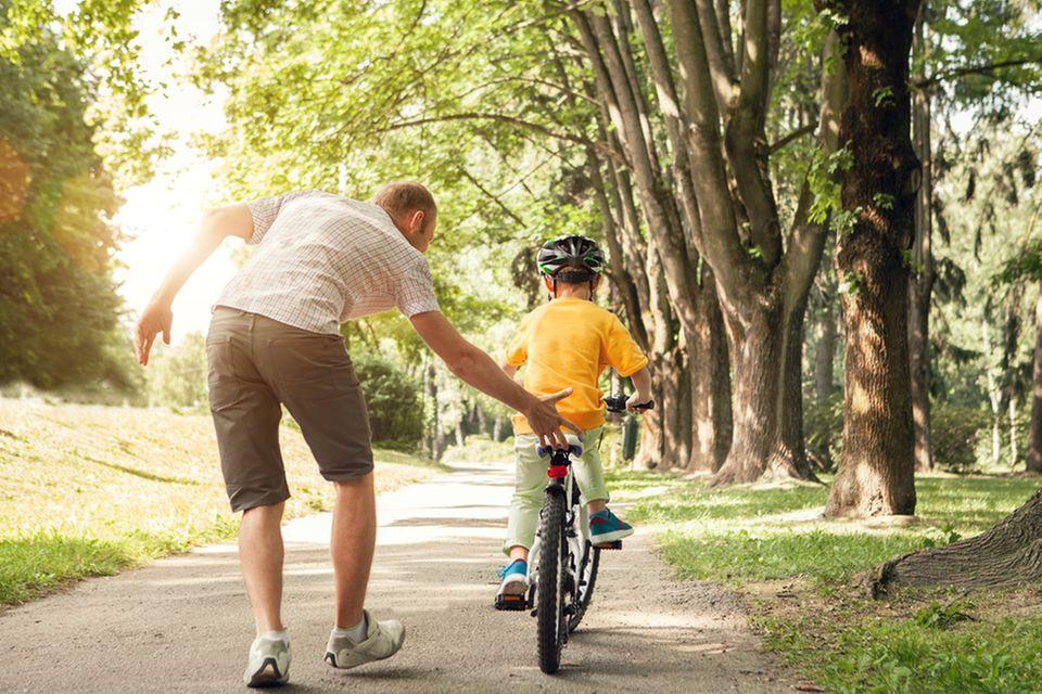 Kind lernt Fahrradfahren mit Papa