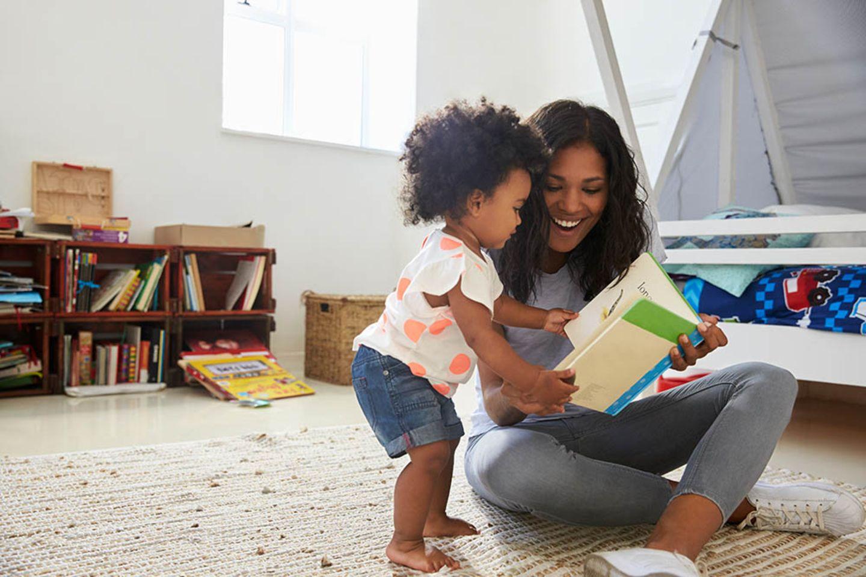 Mutter guckt mit ihrem Kleinkind ein Bilderbuch an