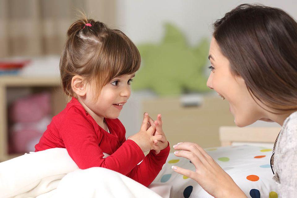 Kleines Mädchen und Frau unterhalten sich intensiv