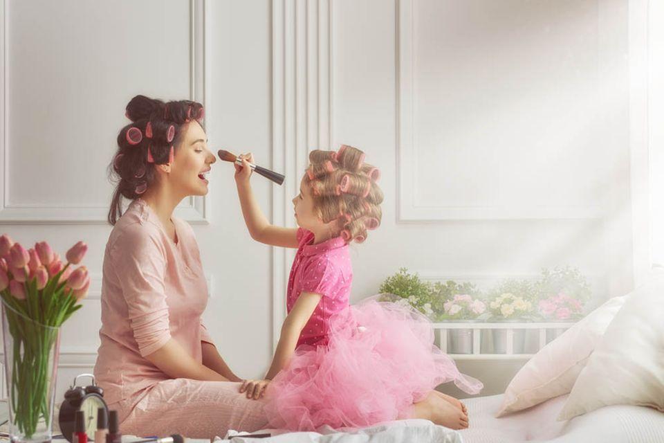 Kleines Mädchen in rosa Tüllrock schminkt junge Frau