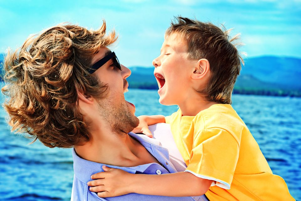 Vater und Sohn toben am Meer