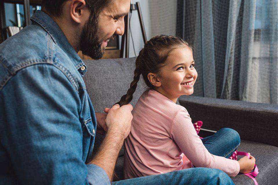 Vater flicht Tochter einen Zopf auf dem Sofa.