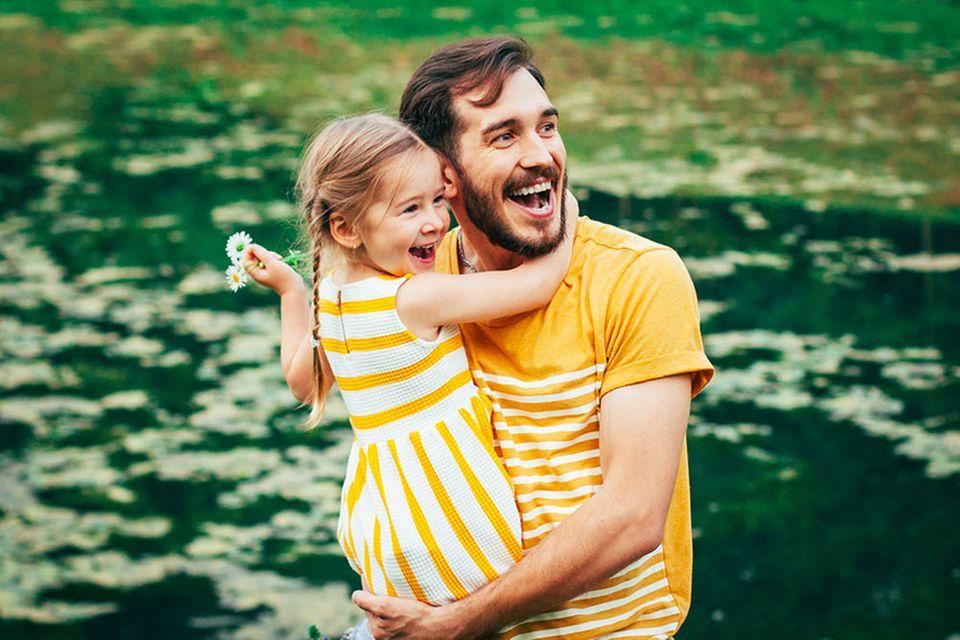 Vater hält Tochter fröhlich am Wasser auf dem Arm.