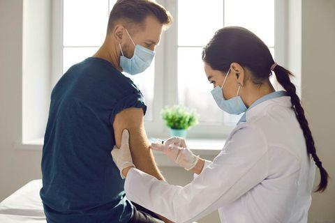 Junger Mann wird con einer Ärztin geimpft