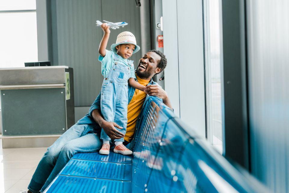 Ein Papa mit seinem kleinen Sohn und Kinderausweis am Flughafen.