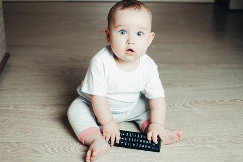 Baby spielt mit Fernbedienung