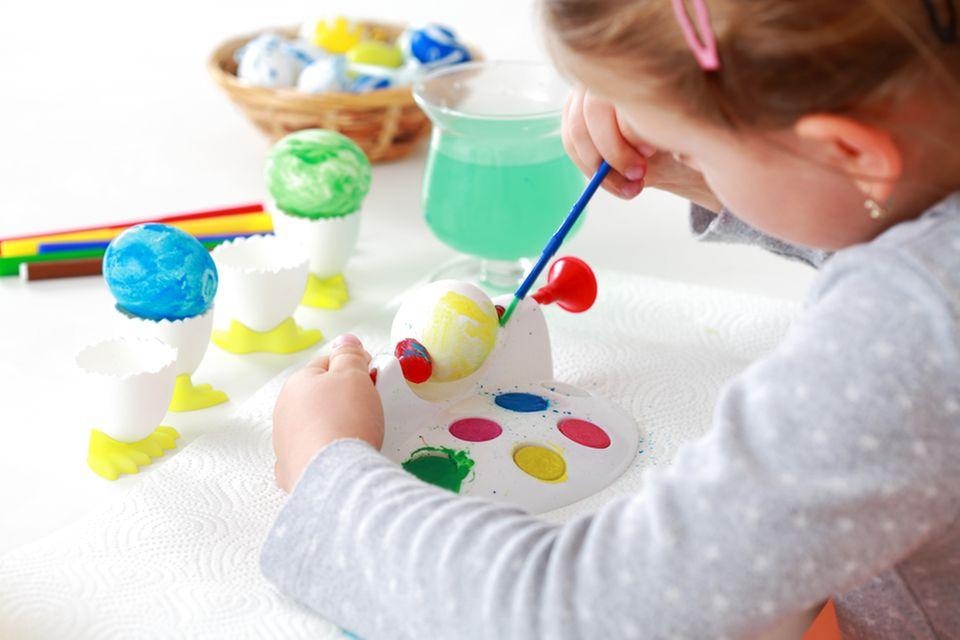 Kleines Mädchen malt Ostereier an