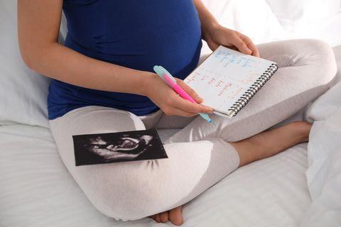 Schwangere macht eine Liste mit Babynamen