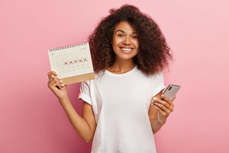 Eine glückliche Frau hält einen Periodenkalender und ihr Smartphone in die Kam