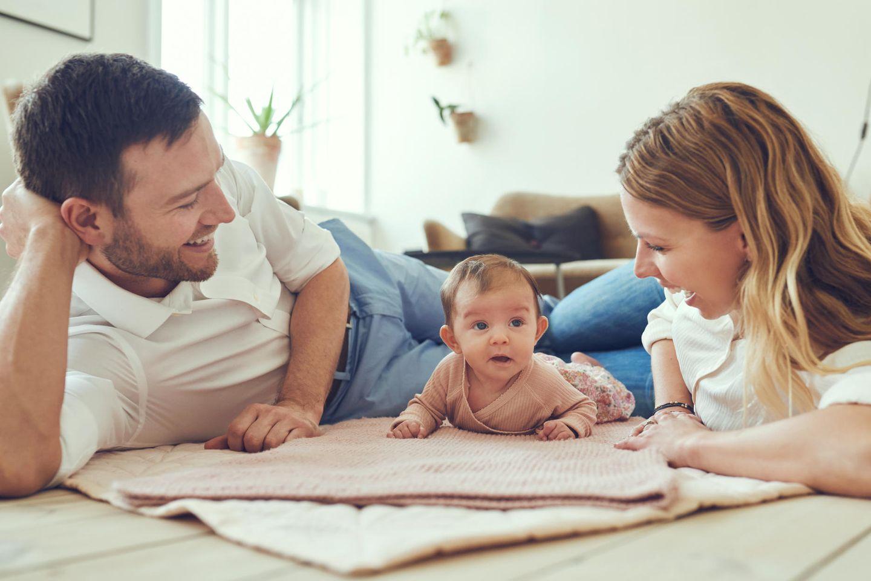 Glückliches Paar mit Baby auf einer Decke