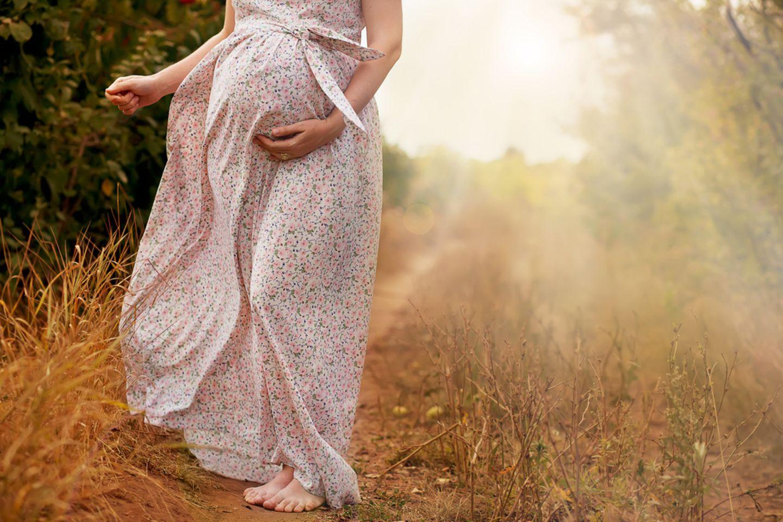 In der Schwangerschaft können auch Haare auf dem Bauch wachsen. Eine Schwangere geht draußen spazieren