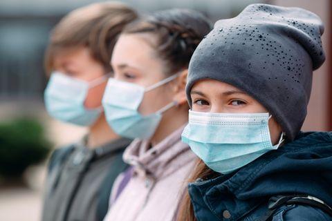 Drei Kinder stehen draußen mit Masken. Immer mehr Kinder erkranken nach einer COVID-19-Infektion an PIMS