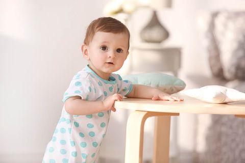 Niedliches Kleinkind steht an einem kleinen Tisch