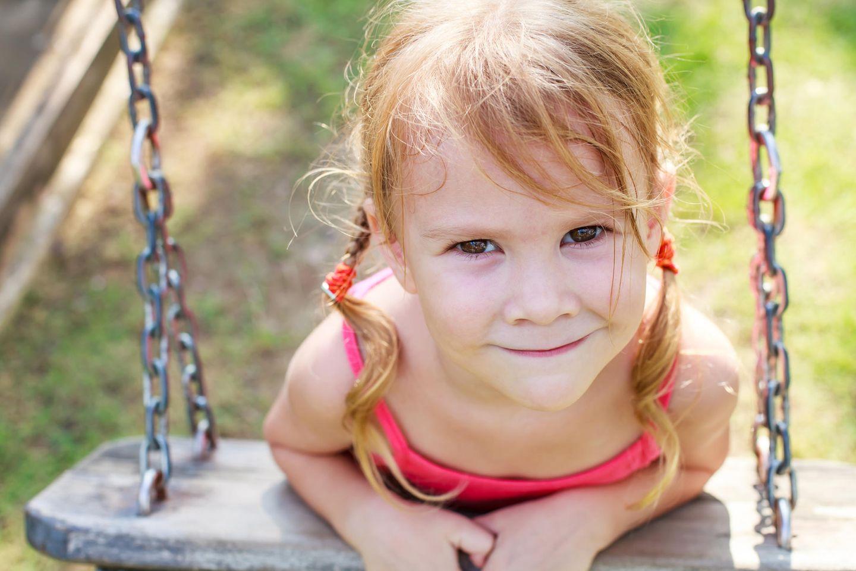 Einzelkinder-Erziehung: Kind auf Schaukel lächelt verschmitzt
