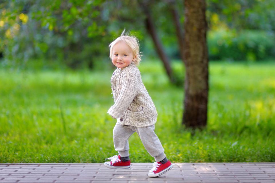 Kleines Mädchen rennt fröhlich durch den Park
