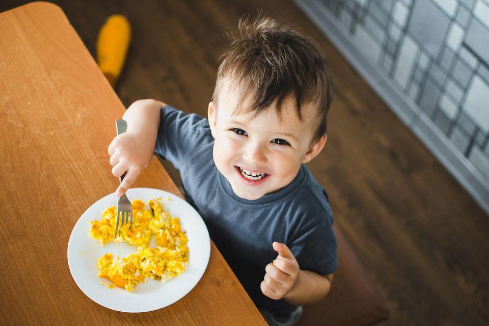 Fröhlicher kleiner Junge isst Rührei