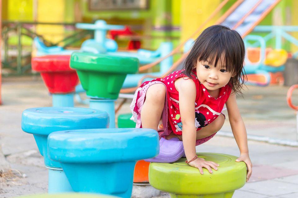 Kleines asiatisches Mädchen auf dem Spielplatz