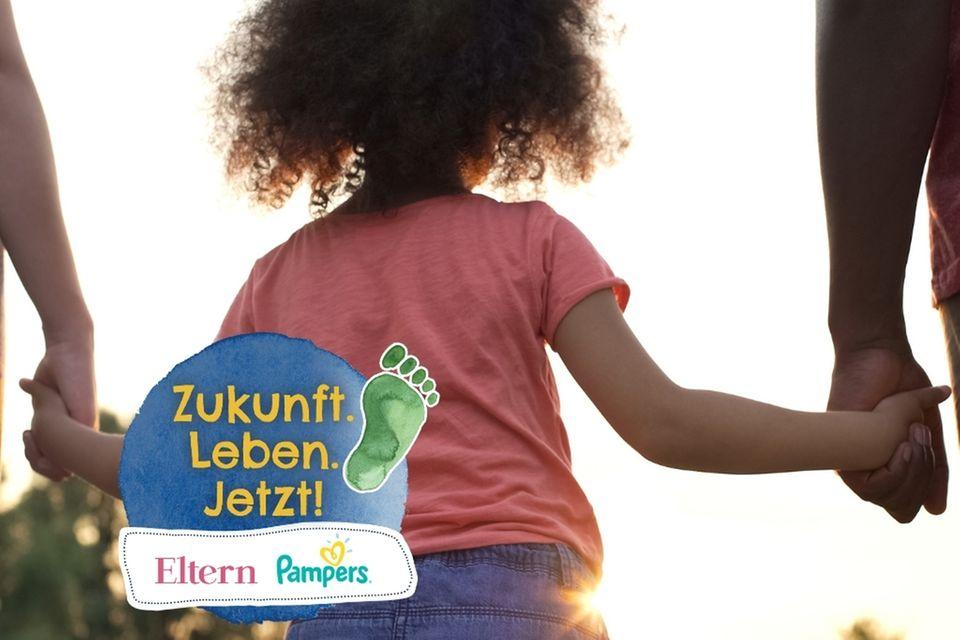 Mädchen an der Hand ihrer Eltern mit Logo