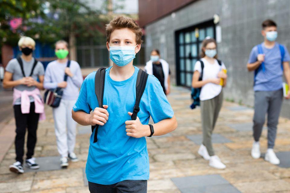 Schüler kommen aus der Schule und tragen medizinische MAsken