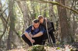 Einfach mal raus: Vater und SOhn suchen im Wald nach Stöcken und Moos