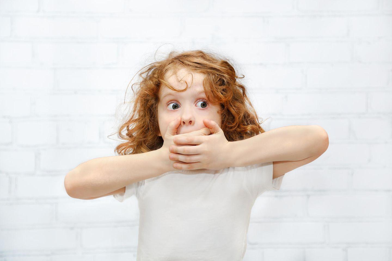 Kind hält sich Hände vor Mund
